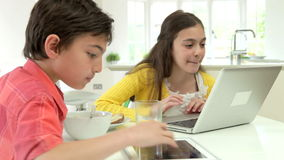 Children With Digital Tablet And Laptop At Breakfast. Children sitting at kitchen counter having breakfast whilst using laptop computer and digital tablet.Shot stock video footage