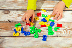 Children digits on the table. Child takes numbers Stock Photography