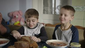 Children dine at the table. Traditional Ukrainian borsch dish. stock footage