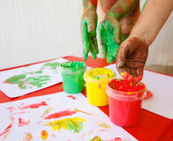 Children dipping fingers in washable finger paints Stock Images