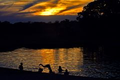 Children dive in the lake at dusk royalty free stock photos