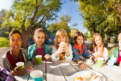 Children diversity drinking tea and eat outside. Children diversity drinking tea from colorful cups and eating cupcakes sitting at white wooden table outside Royalty Free Stock Photography