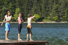 Children diving off a pier. Three children swimming in a lake Stock Image