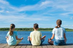 Children do yoga on the pier, by the lake royalty free stock photos