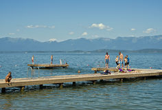 Children on Dock, Montana Lake. Children and teens play on the local municipal swimming dock at Flathead Lake, in northern Montana, a major recreational hub for Stock Photo