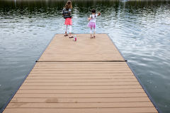Children On Dock Throwing Rocks Royalty Free Stock Photos