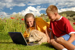 Children with dog at computer. A view of a boy and a girl outdoors with their dog as they playfully try to teach the dog how to use a computer stock photography