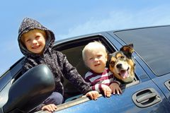 Children and Dog Leaning Out Minivan Window. Two happy young children and their cute German Shepherd dog are leaning out the side window of a blue minivan stock image