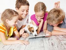 Children and dog with tablet. Group kids playing stock images