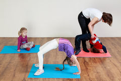 Children are doing a bridge exercise with the help of a trainer Stock Images