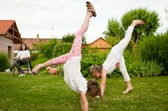 Children doing cartwheels in backyard Royalty Free Stock Images