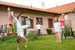 Children doing cartwheels in backyard Royalty Free Stock Image