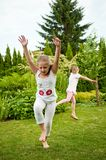 Children doing cartwheels in backyard Stock Photography