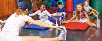 Children doing gymnastics in preschool. Children doing gymnastics in gym of preschool with nursery teacher Stock Photos
