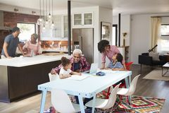 Children Doing Homework In Busy Multi Generation Family Home royalty free stock photo