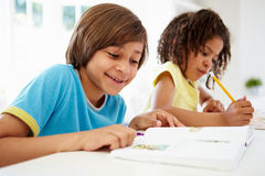 Children Doing Homework In Kitchen Together Stock Photography