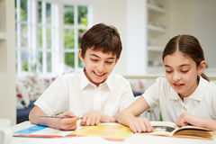 Children Doing Homework In Kitchen Stock Image