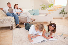 Children doing homework with parents behind them Royalty Free Stock Photo