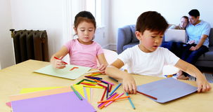 Children doing homework while parents relaxing on sofa. At home stock video footage