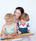 Children doing homework with their mother stock image