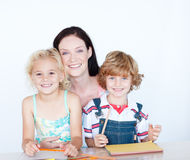Children doing homework with their mother Stock Photo