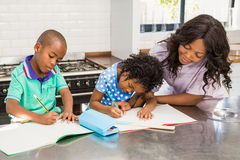 Children doing homework with their mother Stock Photos