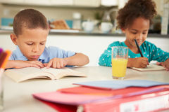 Children Doing Homework Together At Table Stock Photography