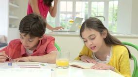 Children Doing Homework Whilst Mother Uses Laptop stock video