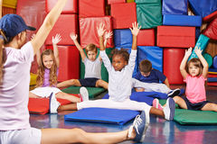 Children doing kids gymnastics in gym. Group of children doing kids gymnastics in gym with nursery teacher