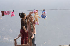 Children doing laundry and playing outdoors. Kids wash their dolls and hang them out to dry on the clothesline. Children doing laundry and playing outdoors Royalty Free Stock Image