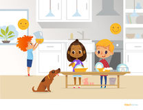 Children doing daily routine activities in kitchen. Two kids washing dishes and red head boy holding pitcher with orange juice. Mo Royalty Free Stock Photo