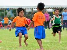 Children doing a teamwork run racing at Kindergarten sport day Stock Images