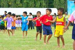 Children doing a teamwork run racing at Kindergarten sport day Royalty Free Stock Photography