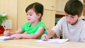 Children doing their homework. In the kitchen stock footage
