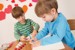 Children doing Valentine's Day Crafts: Love and Hearts. Kids, children, doing Valentine's day arts and crafts with hearts, pencils, paper, love concept Stock Photography