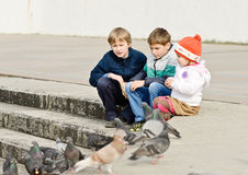 Children and doves. Three children feeding doves in the city royalty free stock image