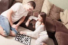 Children with draughts at home. Smile children with draughts at home Royalty Free Stock Images