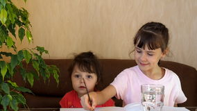 Children draw with colors. Two girls draw houses on the table with paints. A brush is washed in a clear glass of water. stock footage