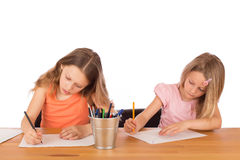 Children draw a drawing. Two concentrated children draw on a wooden table. Isolated on a white background Royalty Free Stock Photography