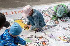 Children draw on the floor with colored markers. Active entertainment of children at the festival royalty free stock photo
