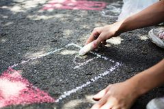Children draw in the park. With chalks of various colors. Selective focus on hand Royalty Free Stock Images