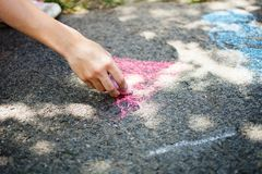 Children draw in the park. With chalks of various colors. Selective focus on hand stock image