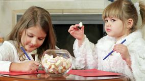 Children draw a pen on a sheet of paper, two girls write, cute kids sitting near the fireplace where the fire is burning stock footage