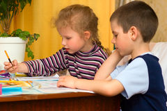 Children draw in pencil. Young children draw in pencil at table Royalty Free Stock Photography
