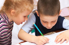 Children draw in pencil. Young children draw in pencil at table Royalty Free Stock Photos
