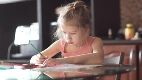 Child of 6 years draws houses sitting at a table. little girl in the morning sun. Children draw with pencils at home sitting at a table. two little girls sister stock video