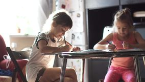 Children draw with pencils at home sitting at a table. two little girls sister draw together in the kitchen.  stock video footage