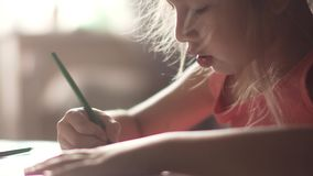 Hairy little girl draws with crayons. little girl in the morning sun. Children draw with pencils at home sitting at a table. two little girls sister draw stock video