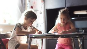 Two little girls draw with crayons sitting at the kitchen table. Children draw with pencils at home sitting at a table. two little girls sister draw together in stock video