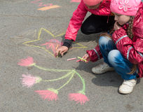 Children drawing on the asphalt. Stock Photos